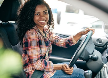 Woman at the drivers seat of a commercial work vehicle